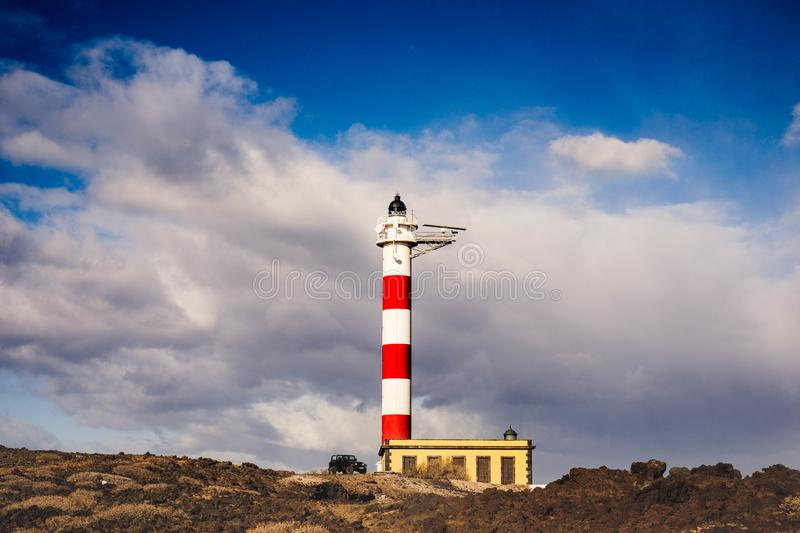 Black offroad car parked near a lighthouse. Spirit of adventure and freedom concept. Black offroad car open parked down a lighthouse in Tenerife. Beautiful sky royalty free stock images