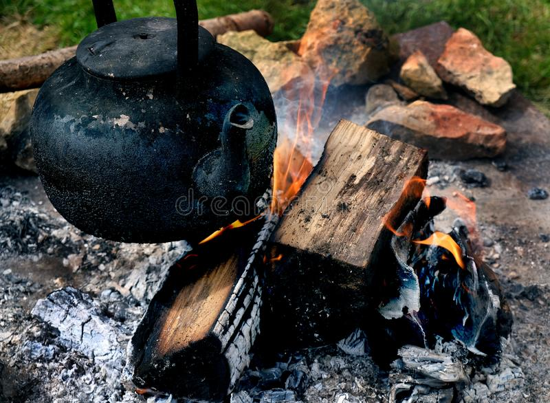 Black old kettle on long camp fire. stock image