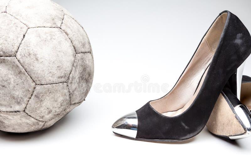 Old ladies shoe on high heels. Black old ladies shoe on high heels on a white background whit an leather football royalty free stock image