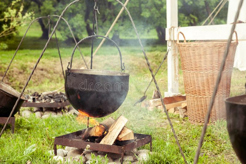 Black old metal pot hanged over fire, camping kitchen.  stock photo