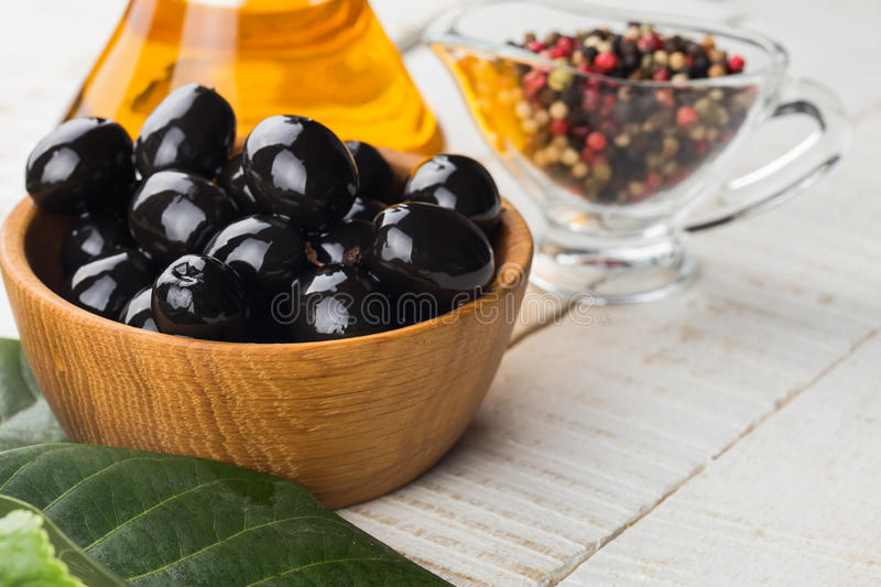Black olive in bowl. Appetizing black olive in bowl on wooden background. Rustic style. Selective focus royalty free stock images