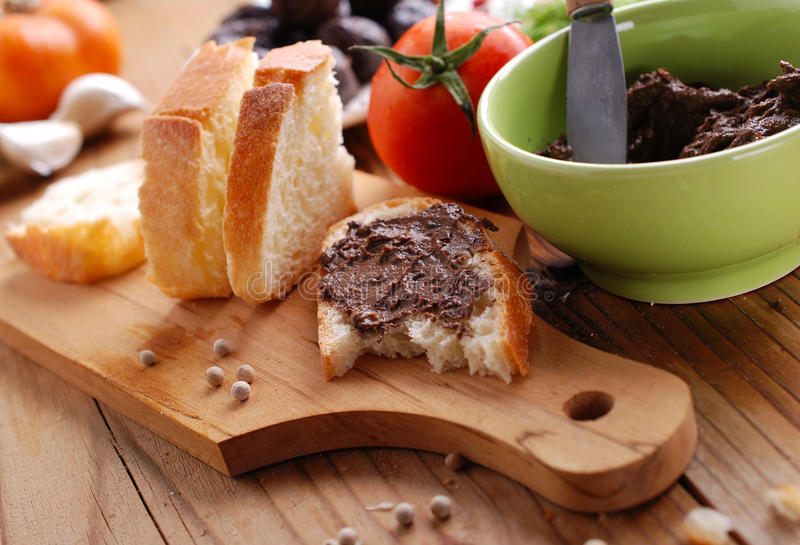 Black olive paté. Black olive pate spread on slice of bread stock photo