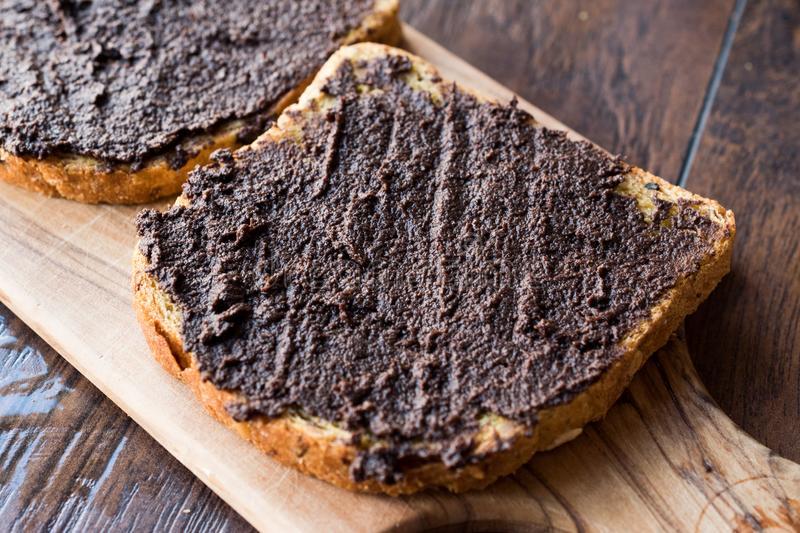 Black Olive Tapenade with Bread. Black Olive Tapenade on Bread with Knife and Jar. Organic Food stock photography