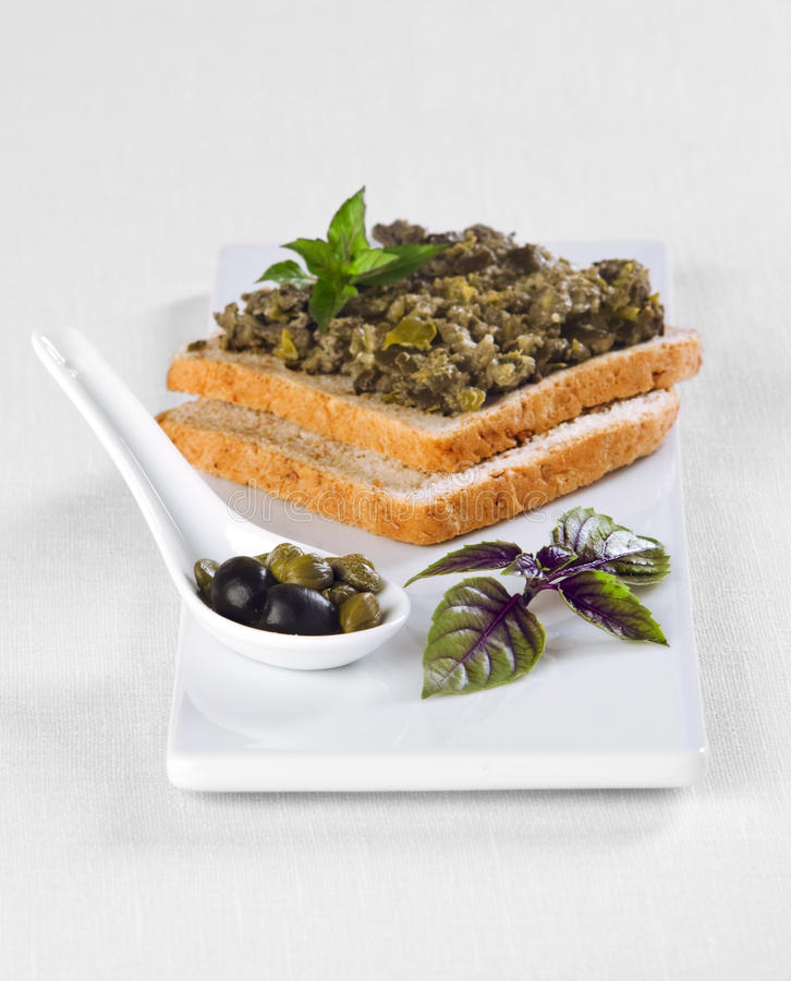 Black Olive Tapenade. With capers and basil on a piece of toast bread stock images