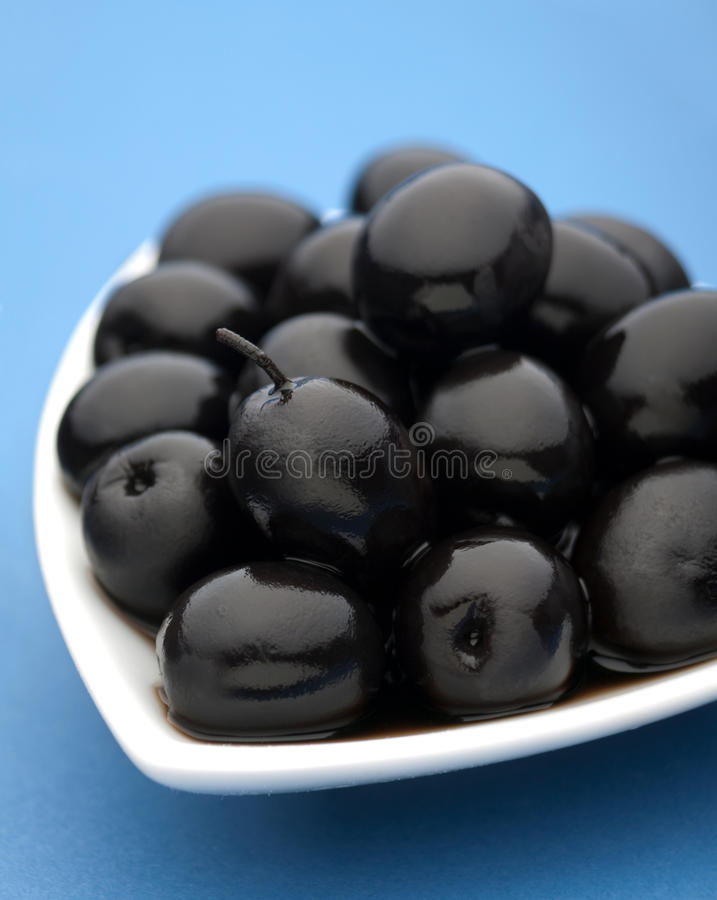 Black olive vegetable. Closeup on blue background royalty free stock photo