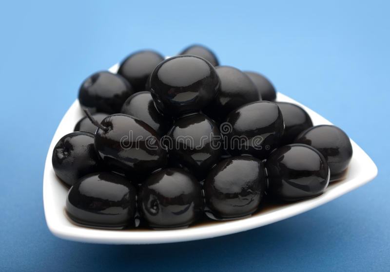 Black olive vegetable. Closeup on blue background stock images