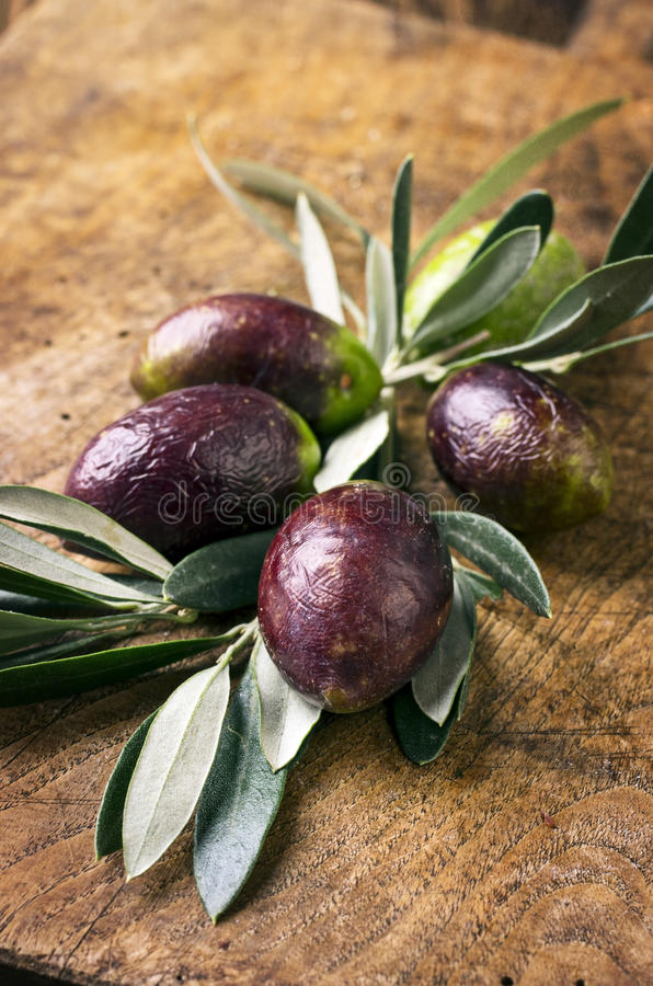 Black Olives. As close-up on old cutting board stock photos