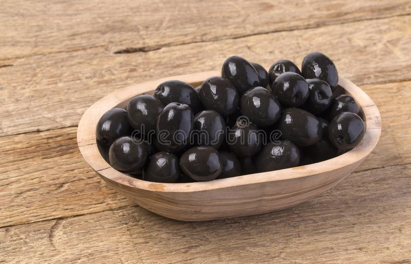 The black olives in bowl. On wooden background stock photo