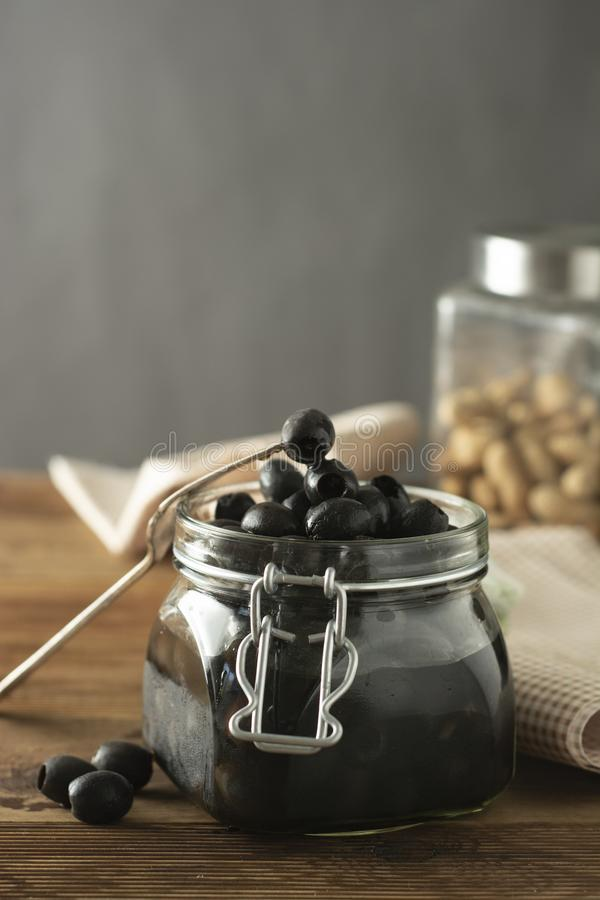 Black olives isolated, mason jar, wooden background. Mediteranian foods.  stock photos