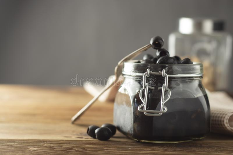 Black olives isolated, mason jar, wooden background. Mediteranian foods. Copy space. Black olives isolated, mason jar, wooden background. Mediteranian foods royalty free stock image