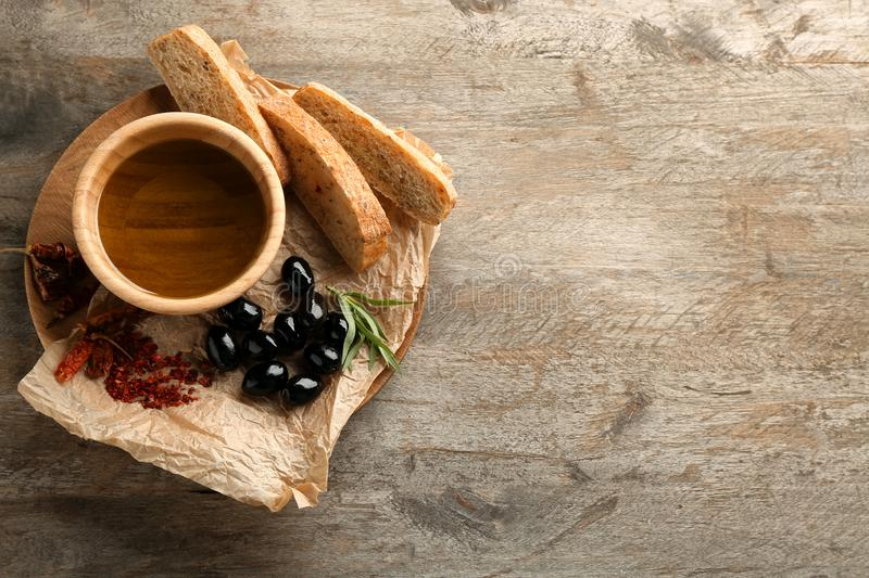 Black olives with oil and bread on wooden table royalty free stock photos