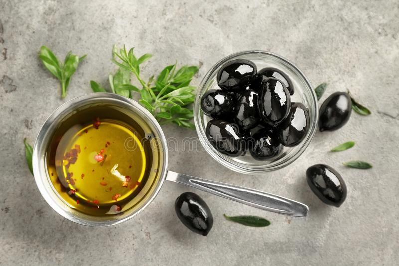 Black olives with oil and herbs on grey textured background stock photography