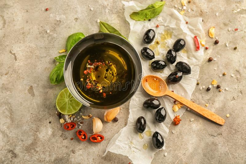 Black olives with oil and spices on grey textured background stock photography