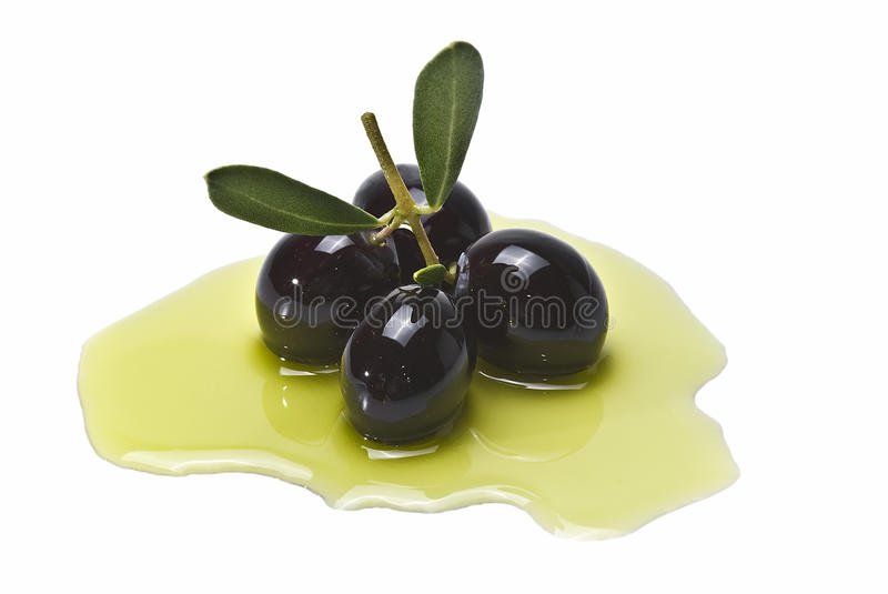 Black olives on olive oil. A branch with four black olives on some olive oil isolated on a white background stock image