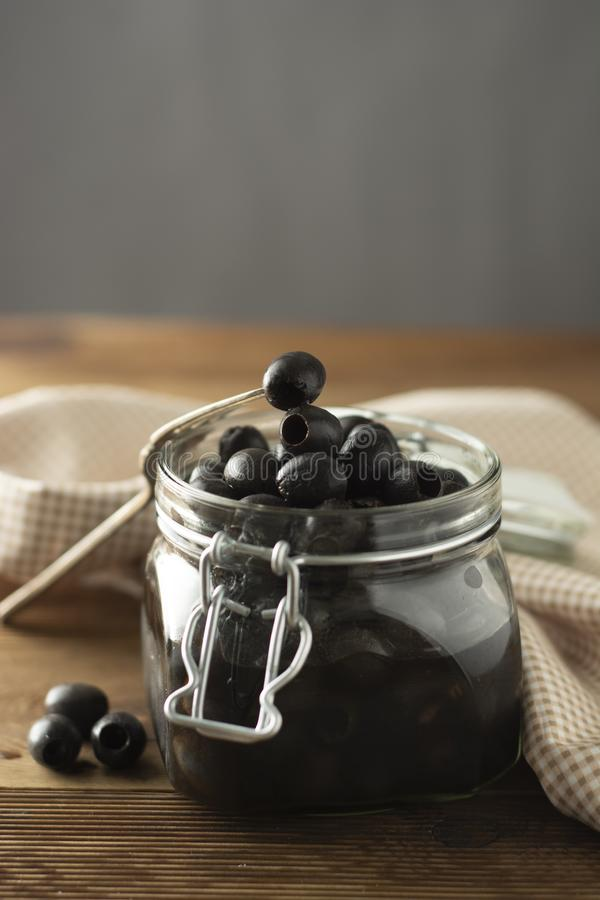Black olives. Pickled homemade olives in glass jar, rustic food style. Vertical image.  royalty free stock photos
