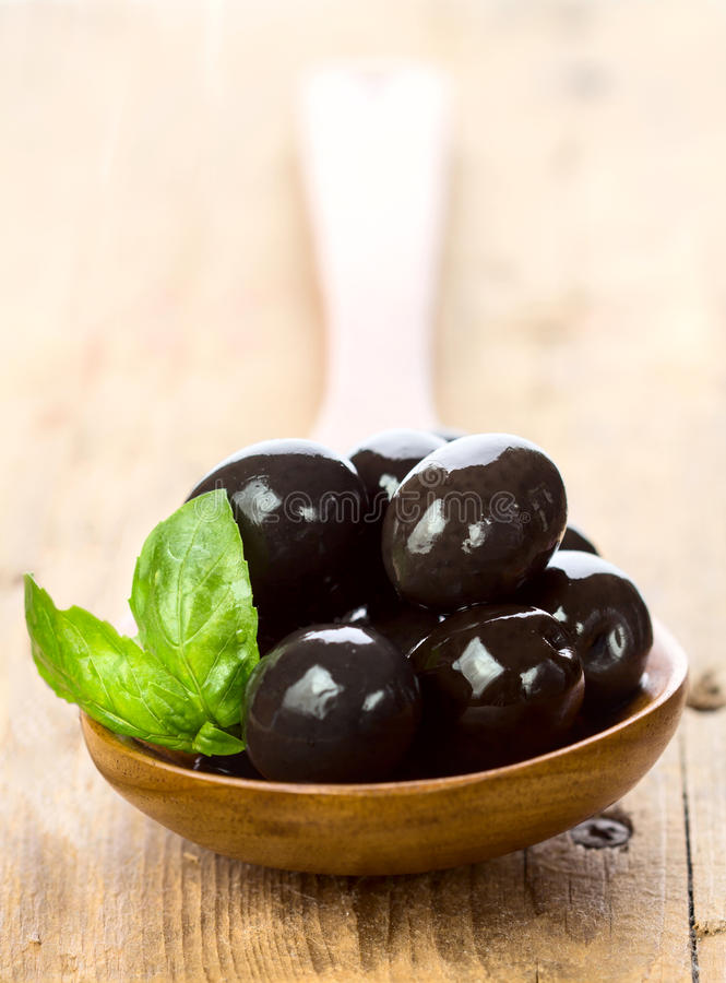 Black olives in a spoon on wooden table. With basil leaves royalty free stock images