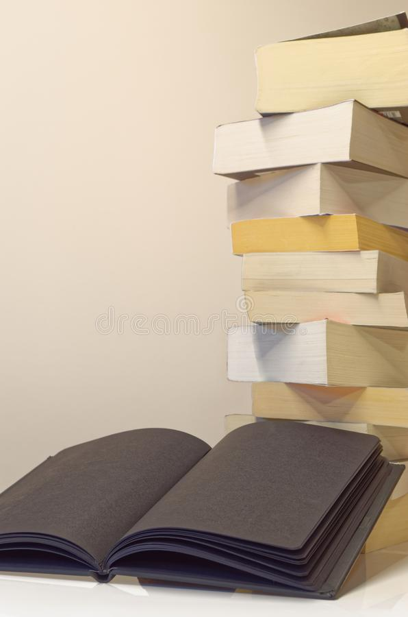 Black open book in foreground of pile of books. On the white table and light grey background stock image