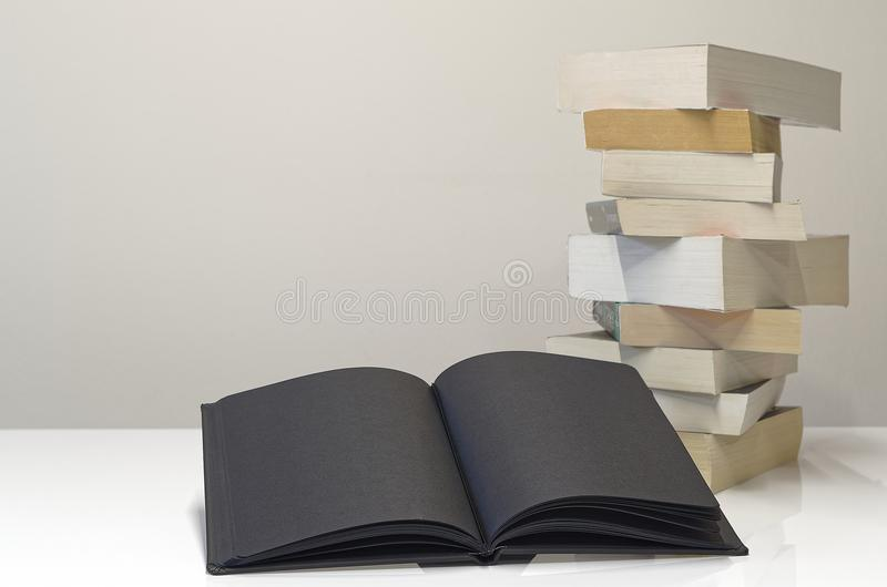 Black open book in foreground of pile of books. On the white table and light grey background royalty free stock photos