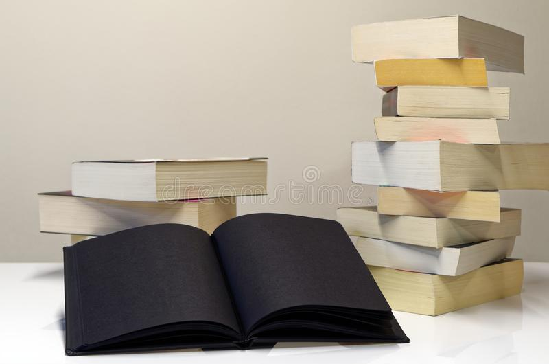 Black open book in foreground of two piles of books. On the white table and light grey background stock images