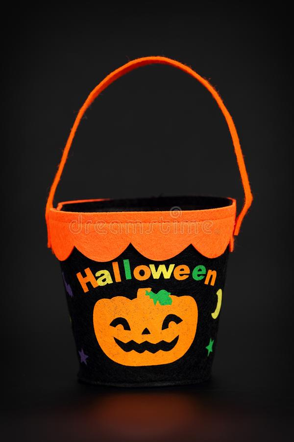 Black and orange fabric Trick-or-Treat basket / Candy Bucket on black background with reflection. Halloween related object stock photos