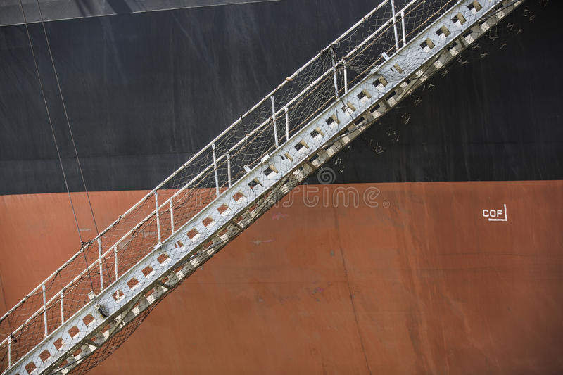 Black orange Iron Ore Carrier with lowered gangway. Ready for people to go aboard the vessel royalty free stock images