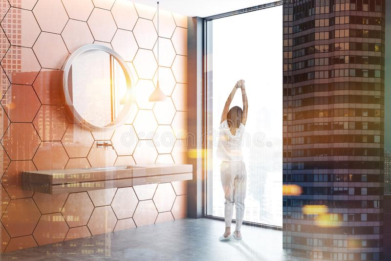 Black and orange loft bathroom, double sink, girl. Woman in bathroom with orange honeycomb pattern and black walls, concrete floor, loft window and white stock photo