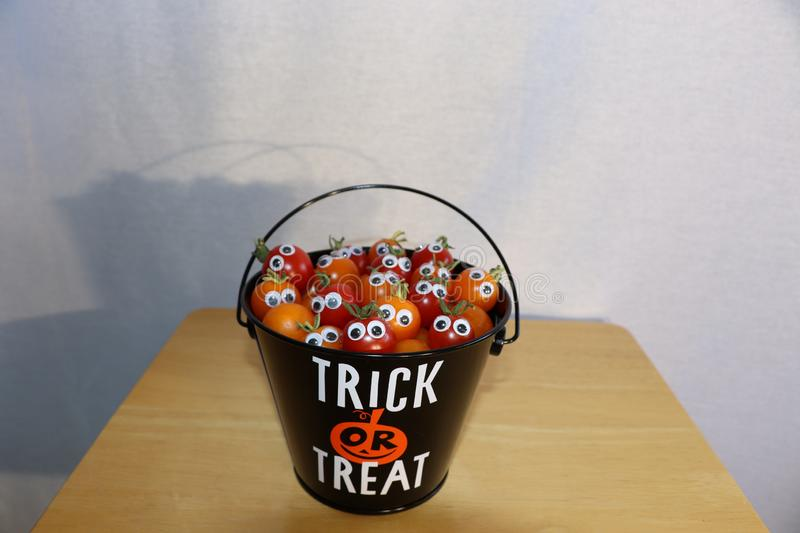A black and orange trick or treat bucket full of mini tomatoes with googly eyes. A small trick or treat bucket full of mini tomates with googly eyes peeking out stock photos