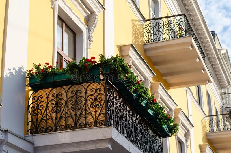 Black ornate wrought iron balcony decorated with flowers. Boxes with red geraniums. Bottom side view royalty free stock photography