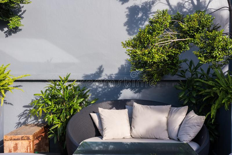 Black outdoor furniture round rattan armchairs and glass table. With wall and trees stock images