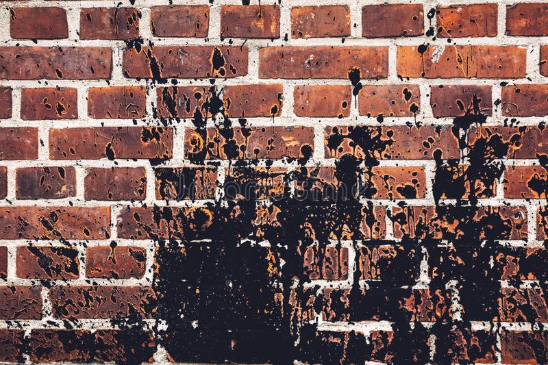 Black paint spilled all over red brick wall. royalty free stock photography