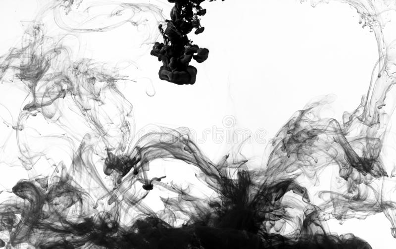 Black paint swirling in water. On white background royalty free stock photography