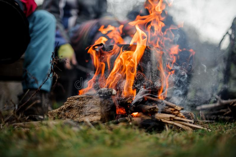 Black pan standing inside the bonfire on the background of the group of friends. Black pan with a dish standing inside the bonfire on the background of the group royalty free stock image