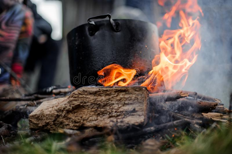 Black pan standing on the campfire on the background of the group of people. Black pan with a dish standing on the campfire on the background of the group of stock images