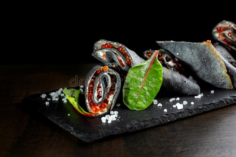 Black pancakes stuffed with red salmon caviar. stock image