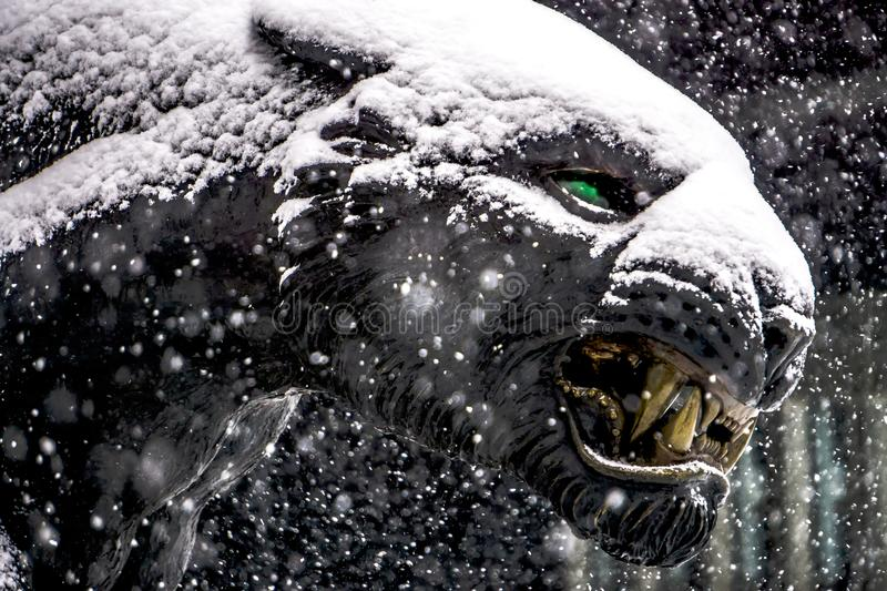 Black panther statue seen through falling snow flakes royalty free stock photography