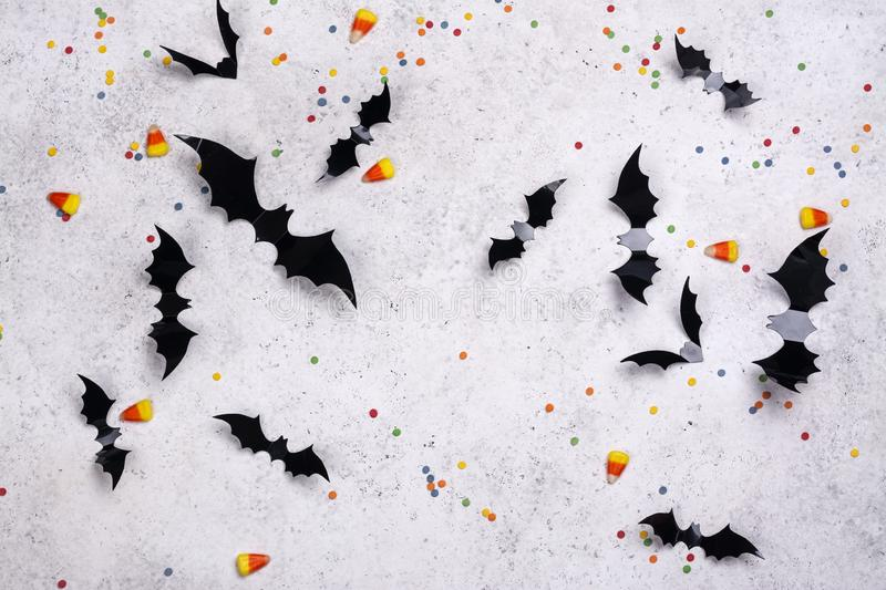 Black paper bats on a stone wall. Wall decor for Halloween - paper bats, sprinkles and candy corns on stone background. Copy space stock image