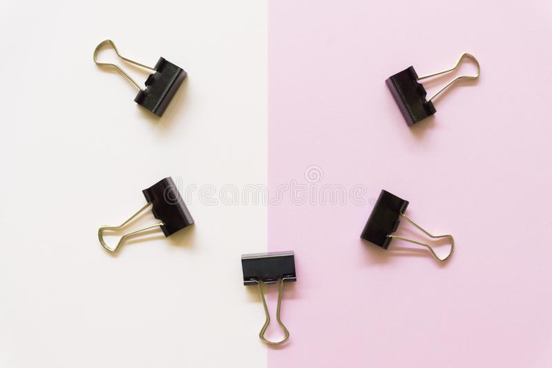 Black paper cilps on white and pink background stock photos
