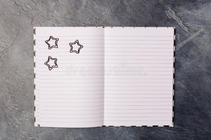 Black paper clips on opened blank copybook, laying on dark black abstract background with copy space, minimal style. Black paper clips on opened blank copybook royalty free stock photography