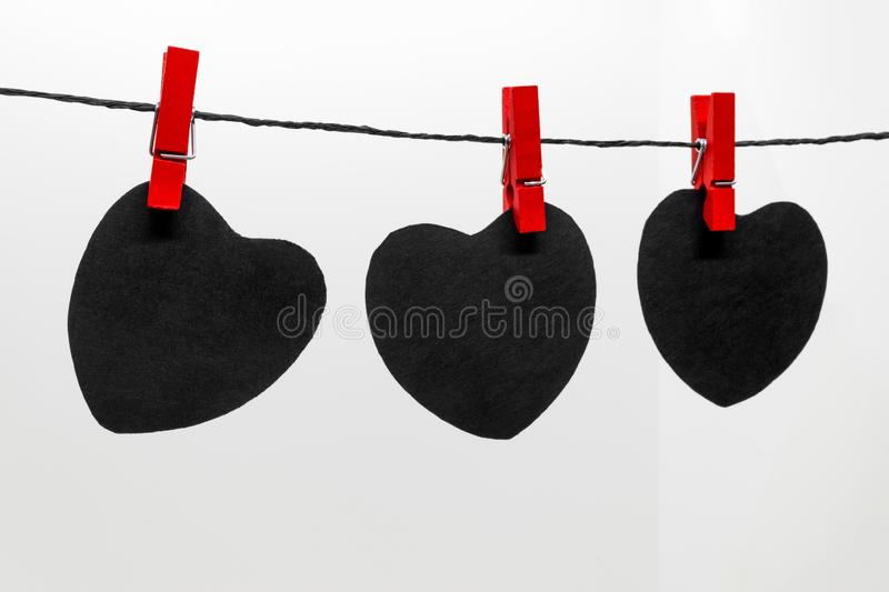 Lack paper hearts with copy space hanging on black rope and attached with red laundry pins stock images