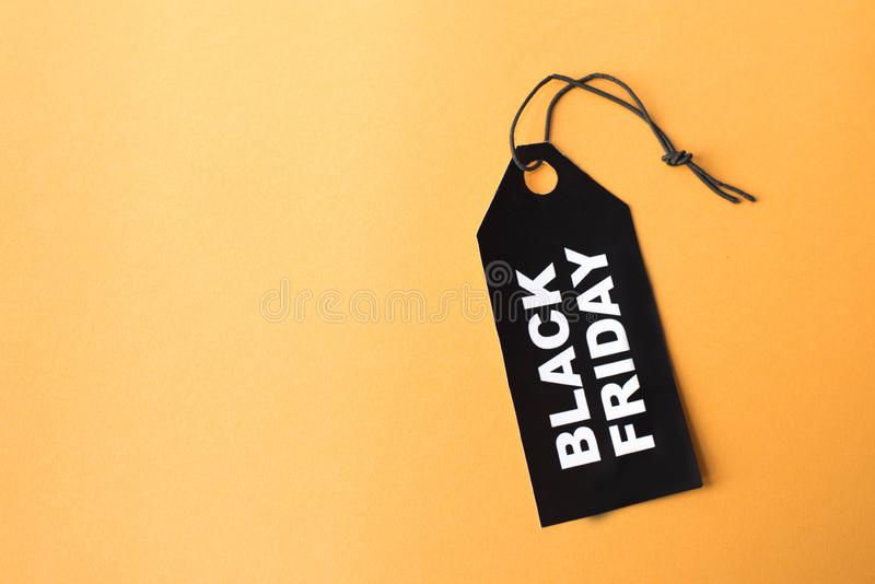 Black paper label with the text black friday on orange background.  royalty free stock photos