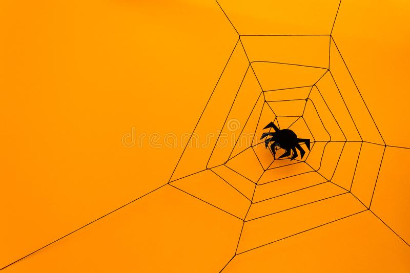 Black paper spider with web on yellow background. Halloween concept. Paper cut style. Top view royalty free stock image