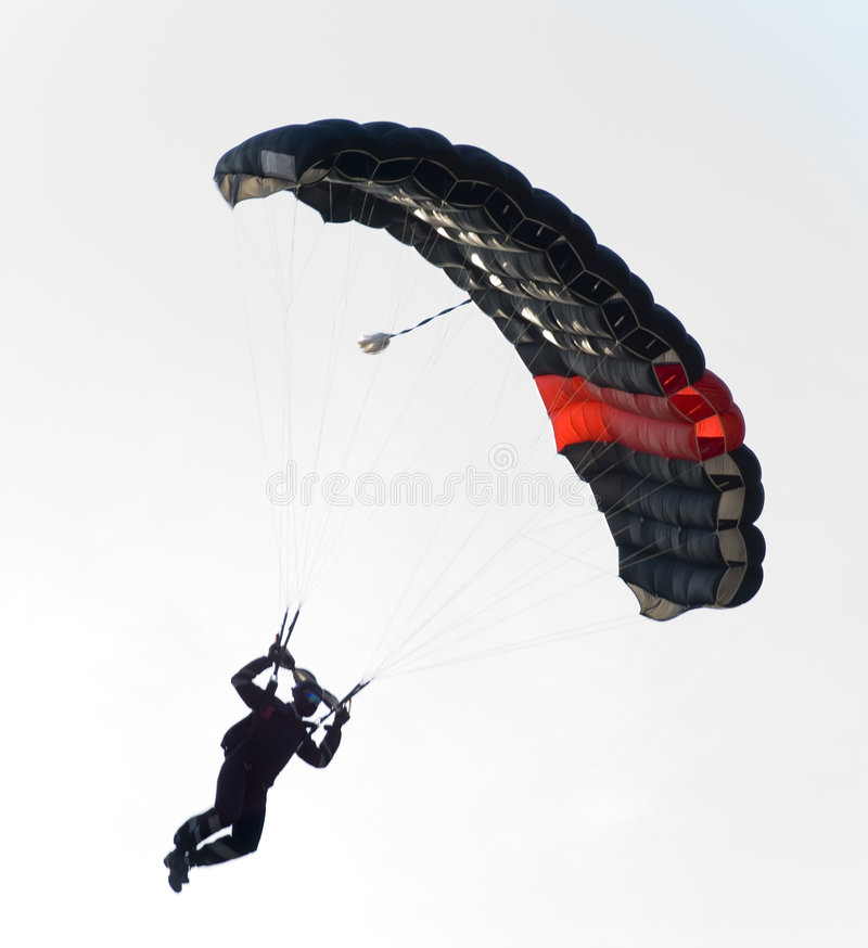 Black parachute flying. A contrast between a black parachute and skylight. The Sun is almost behind the parachutist, but it's not catched with camera stock photography