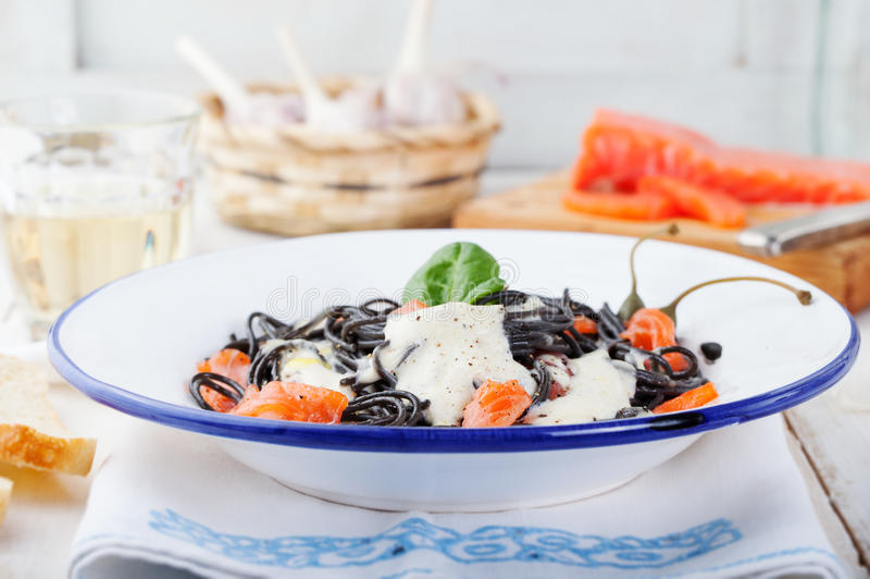 Black pasta spaghetti with cream sauce and smoked salmon Italian cuisine stock photos