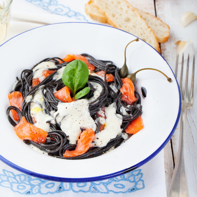 Black pasta spaghetti with cream sauce and smoked salmon Italian cuisine royalty free stock photos