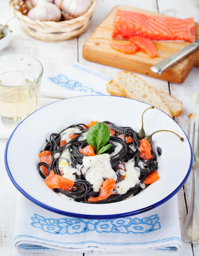 Black pasta spaghetti with cream sauce and smoked salmon Italian cuisine royalty free stock images