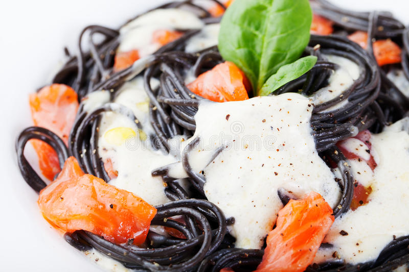 Black pasta spaghetti with cream sauce and smoked salmon Italian cuisine royalty free stock photography