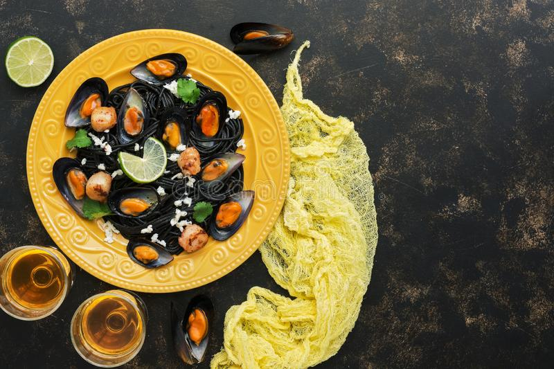 Black pasta spaghetti with mussels, scallops and white wine on a rustic background. Mediterranean food. Top view, copy space stock photography