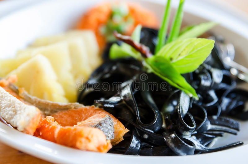 Black pasta spaghetti with smoked salmon Italian stock photo