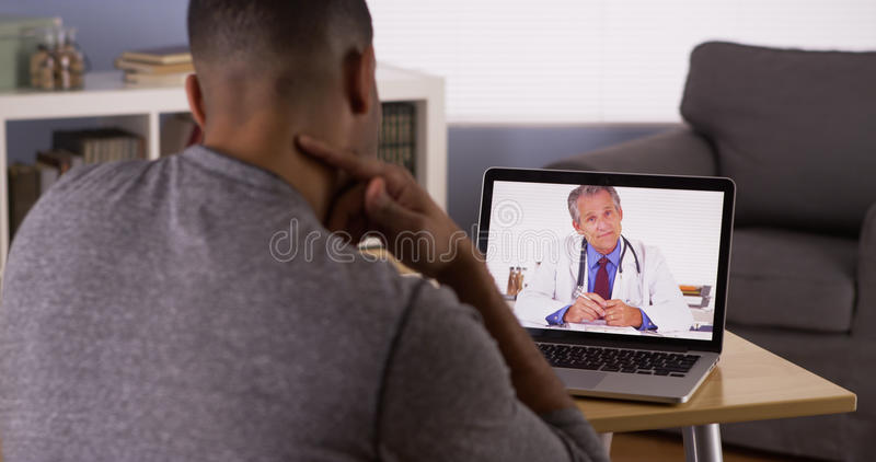 Black patient talking to senior doctor on laptop. Black patient talking to doctor on laptop stock images