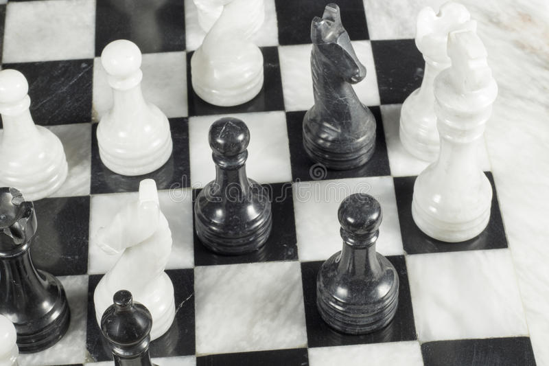 Black pawn gives checkmate to white king. Marble chess board. Elegant chessboard and pieces made of marble. Black pawn gives checkmate to white king royalty free stock photo